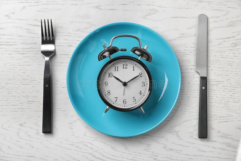 Composition with alarm clock, plate and utensils on light background. Flat lay composition with alarm clock, plate and utensils on light background royalty free stock photo