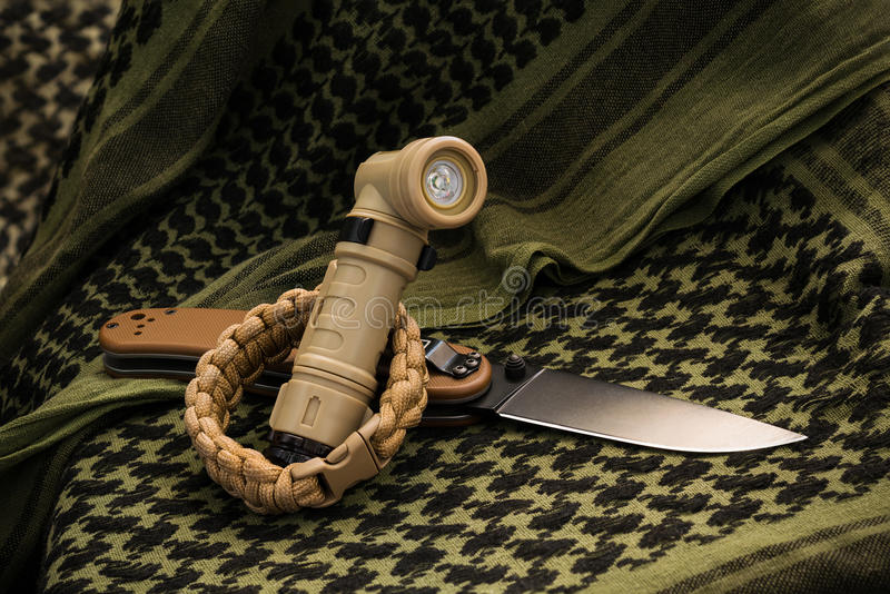 Composition of angle-head flashlight, paracord bracelet and fold royalty free stock photos