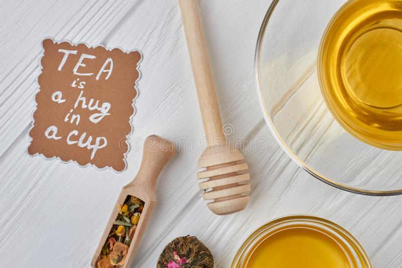 Composition with aromatic healthy tea on wooden background. Herbal tea, honey, dry tea and paper card. Tea is a hug in a cup royalty free stock photos