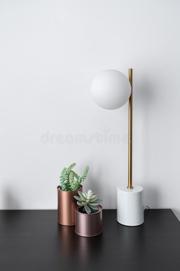 Composition of artificial plants copper vase and gold stylish table lamp in mid century modern design standing on black wooden top royalty free stock images