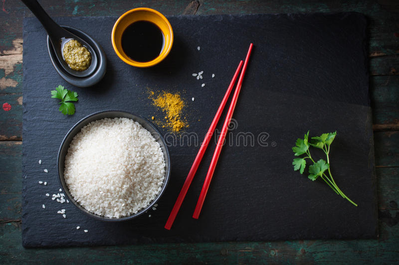Composition with asian food - rice for sushi, spices, sauces and chopsticks stock photo