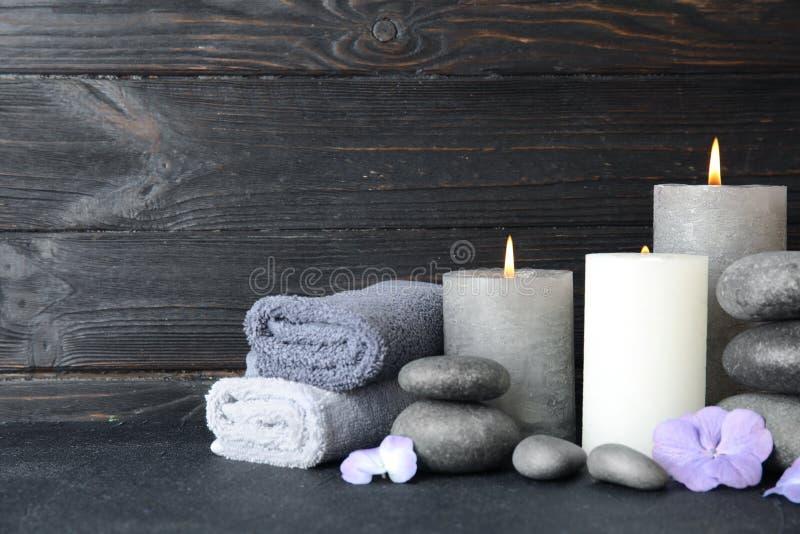 Composition avec des pierres, des serviettes et des bougies de zen sur la table sur le fond en bois photographie stock