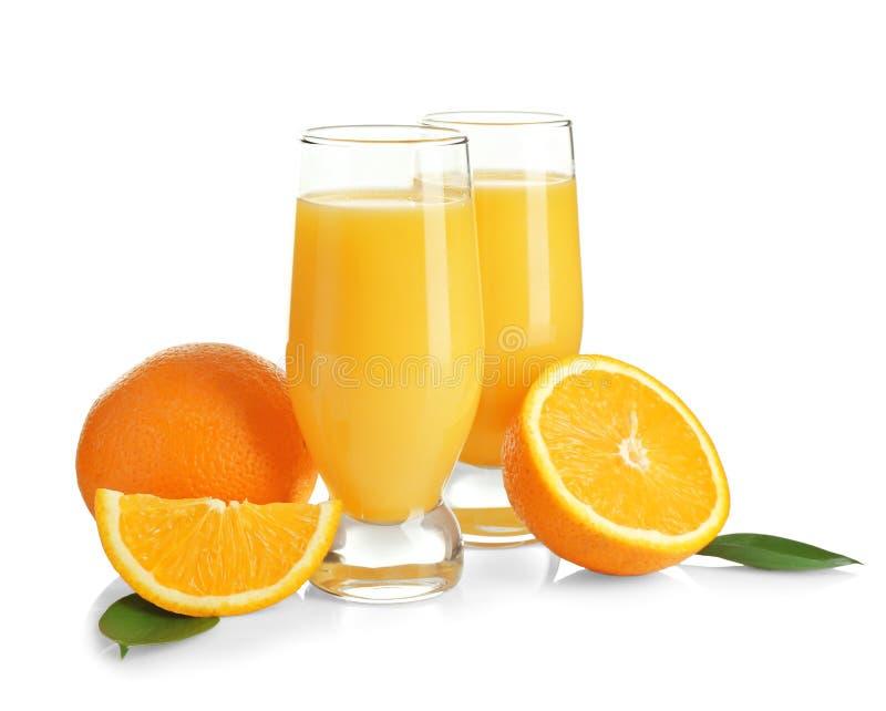 Composition avec des verres de jus et d'oranges frais photos stock