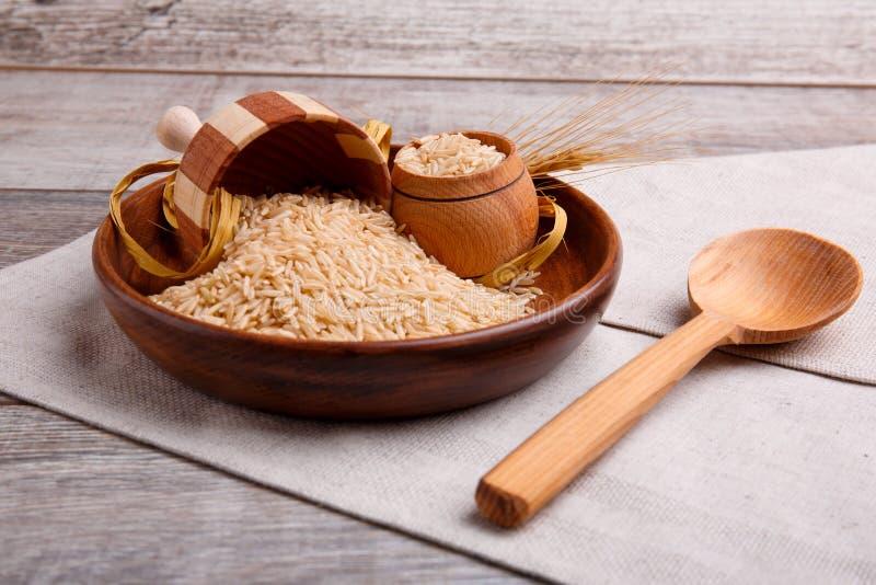 Composition avec du riz cru dans une cuvette brune en bois avec une spatule en bois et une cuillère photos libres de droits
