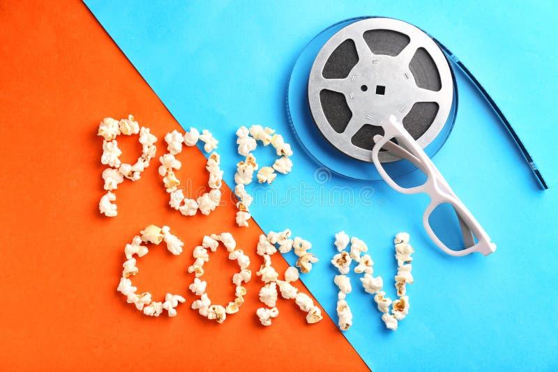Composition avec la bobine de MAÏS et de film des mots POP sur le fond de couleur photographie stock libre de droits