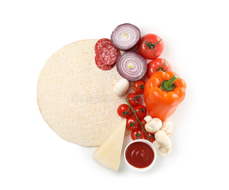 Composition avec la croûte de pizza et les ingrédients frais d'isolement sur le blanc image libre de droits