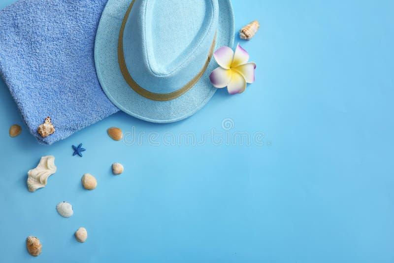 Composition avec la serviette, le chapeau et les coquillages de plage sur le fond de couleur image libre de droits