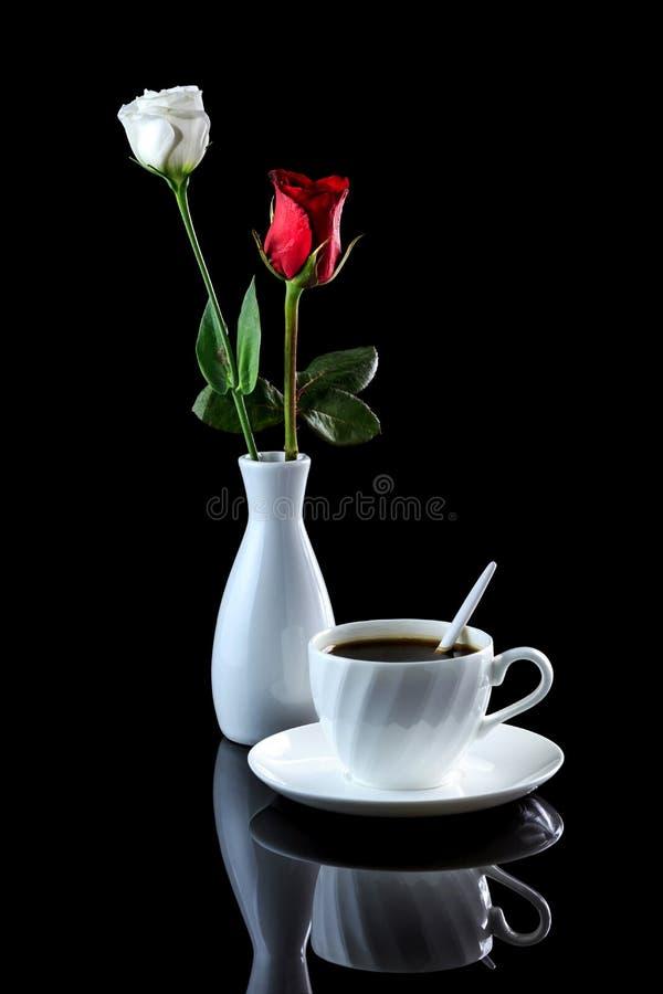 Composition avec la tasse de la rose de café, blanche et rouge sur un noir au sujet de photo libre de droits