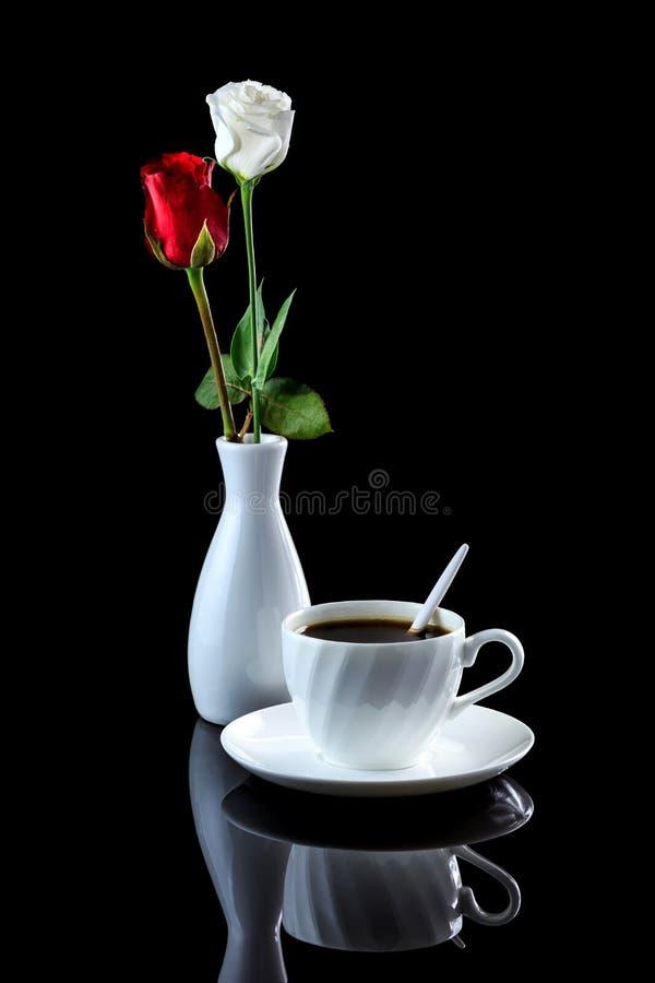 Composition avec la tasse de la rose de café, blanche et rouge sur un noir au sujet de photos stock