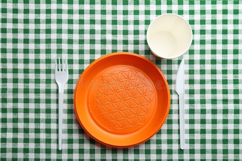Composition avec le dishware en plastique sur la nappe à carreaux photo libre de droits