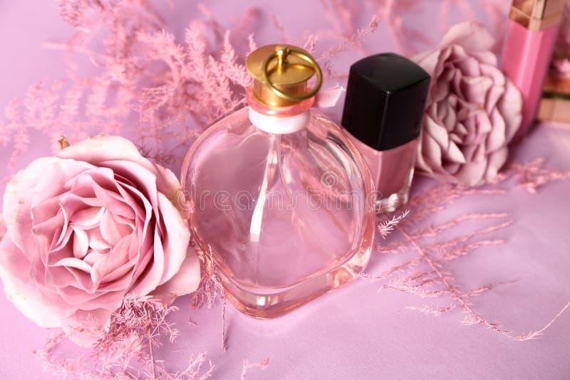 Composition avec le parfum, les cosmétiques et les roses sur le fond rose image stock