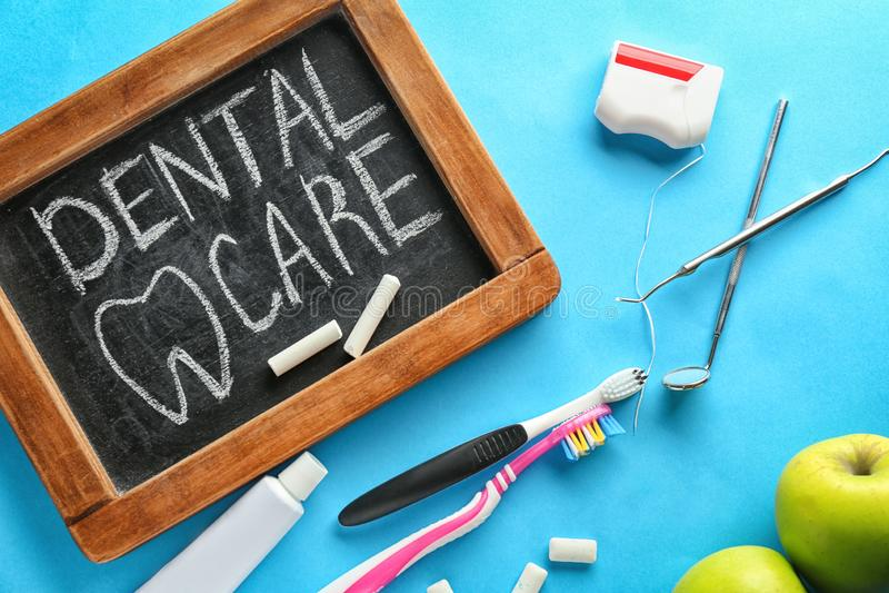 Composition avec le tableau noir et l'équipement dentaire d'hygiène sur le fond de couleur Concept sain de dents image stock