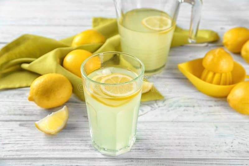 Composition avec le verre de jus de citron et de citrons frais photographie stock