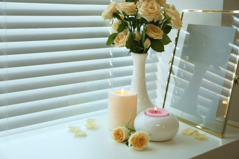 Composition avec les bougies brûlantes, les roses fraîches et le cadre de photo sur le filon-couche de fenêtre photographie stock libre de droits