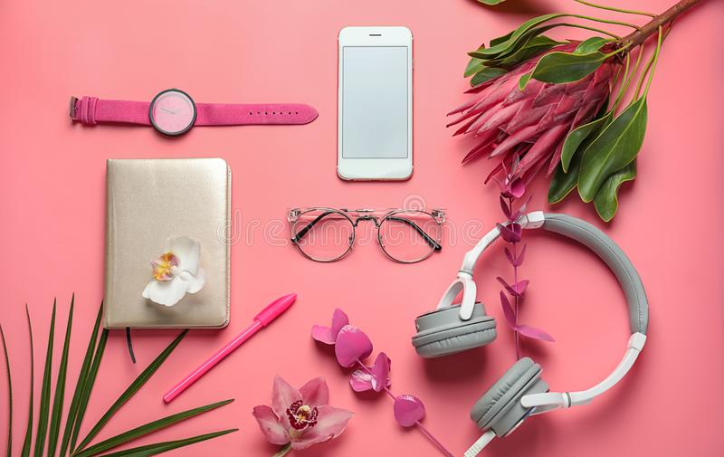 Composition avec les fleurs, le téléphone portable et les écouteurs tropicaux sur le fond de couleur photographie stock libre de droits