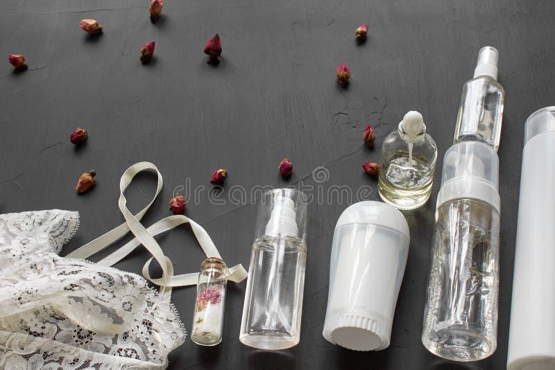 Composition avec les produits cosmétiques de soins de la peau sans label et lingerie blanche sur un fond de bureau noir images libres de droits