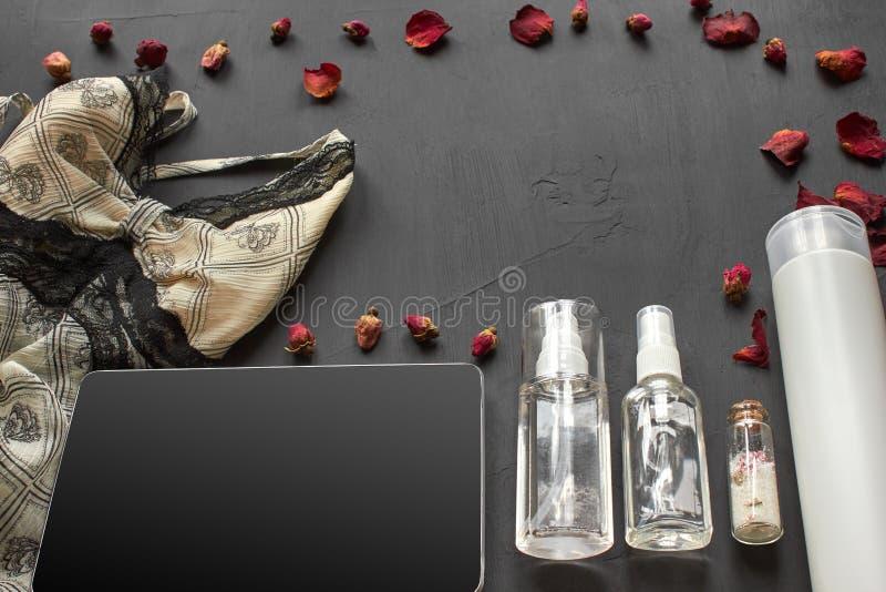 Composition avec les produits cosmétiques de soins de la peau sans lingerie de label et de dentelle sur un fond de bureau noir images stock