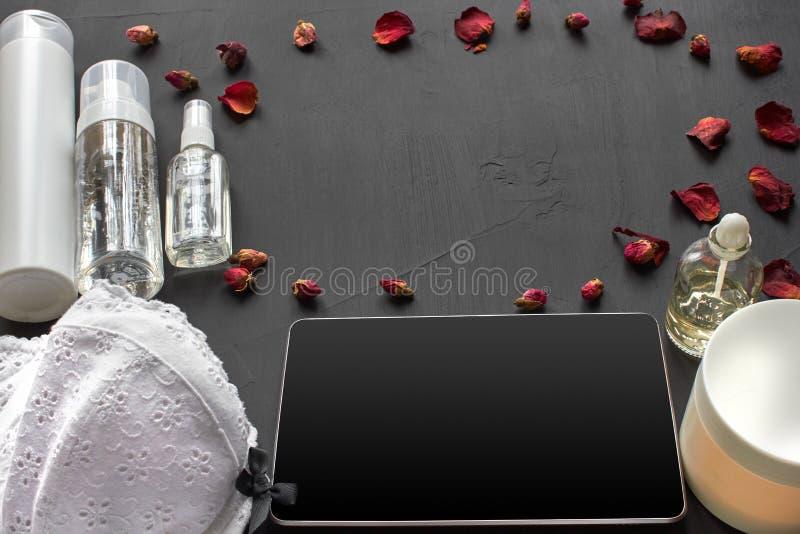 Composition avec les produits cosm?tiques de soins de la peau sans label et lingerie blanche sur un fond de bureau noir photos libres de droits