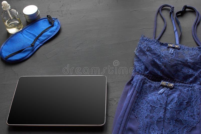 Composition avec les produits cosm?tiques de soins de la peau sans label et lingerie blanche sur un fond de bureau noir images libres de droits