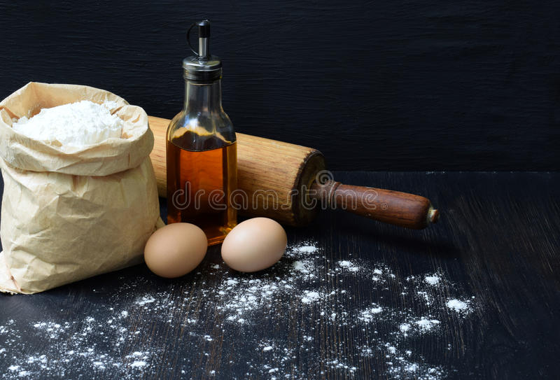 Composition of bag of wheat flour, eggs, oil and rolling pin. Preparation for kneading dough, baking on dark background. Space for stock images