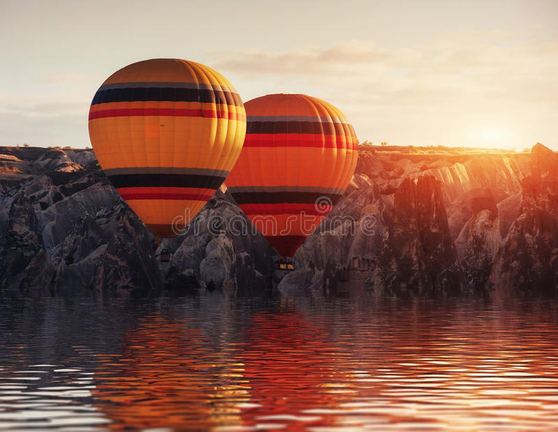 Composition of balloons over water and valleys, gorges, hills, b stock image