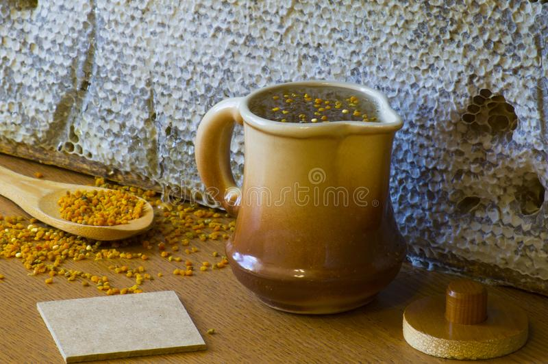 Composition of bee products, bright yellow and orange flower pollen on a wooden spoon stock photos
