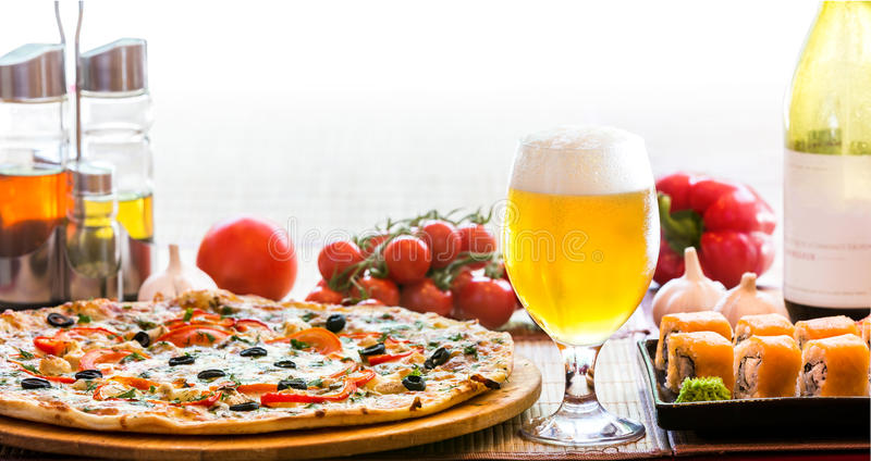 Composition of beer sushi and pizza stock images