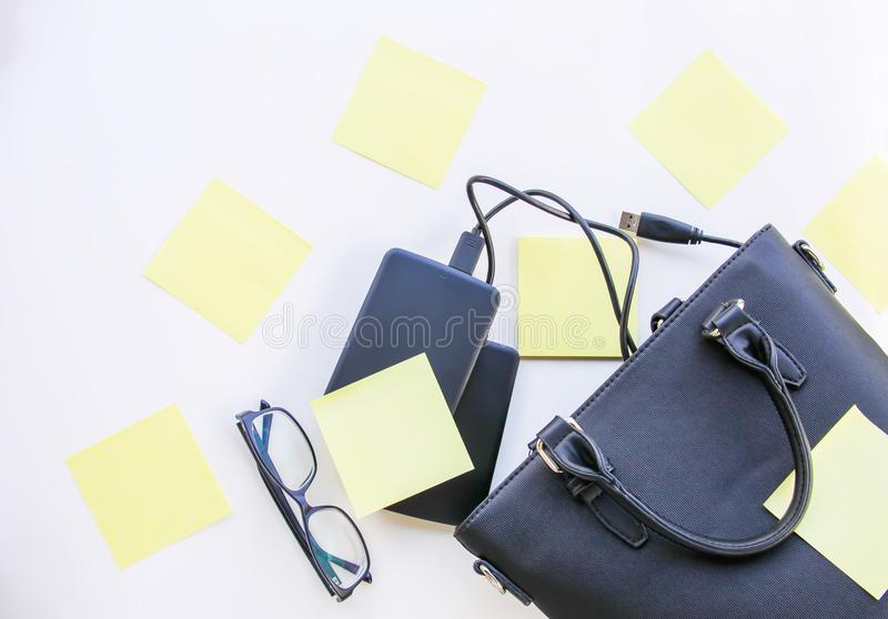 Composition with black bag, hard disks, colorful paper empty stickers and glasses. stock photography