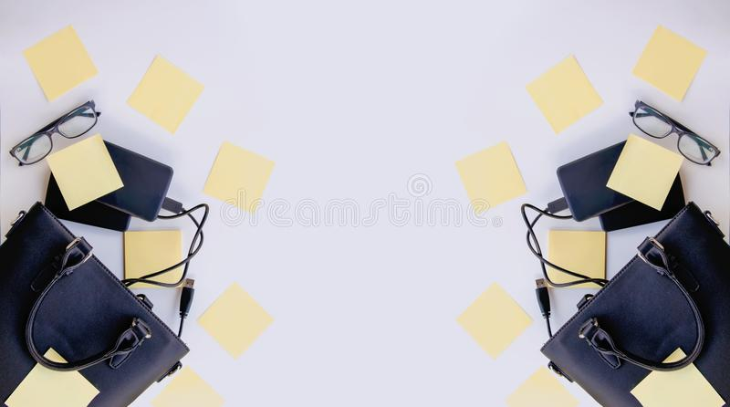 Composition with black bag, external hard disks, colorful paper empty stickers and glasses. Business details. Symmetrical banner composition with black bag stock images
