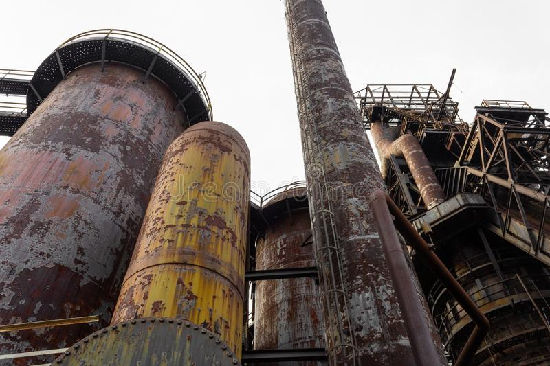 Composition of blast furnaces and smokestacks in an old steel mill, rust and peeling paint patinas royalty free stock image