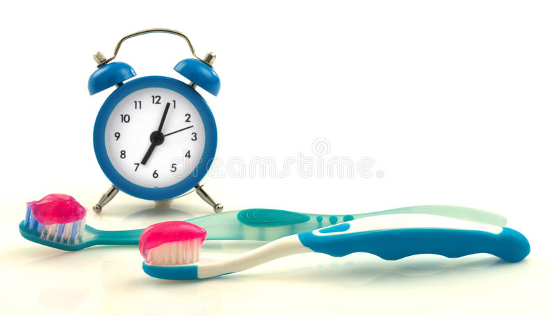 Composition from blue clock and toothbrushes with magenta toothpaste stock photography