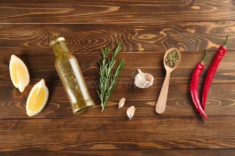 Composition with bottle of tasty sauce and condiments on wooden background, flat lay stock image