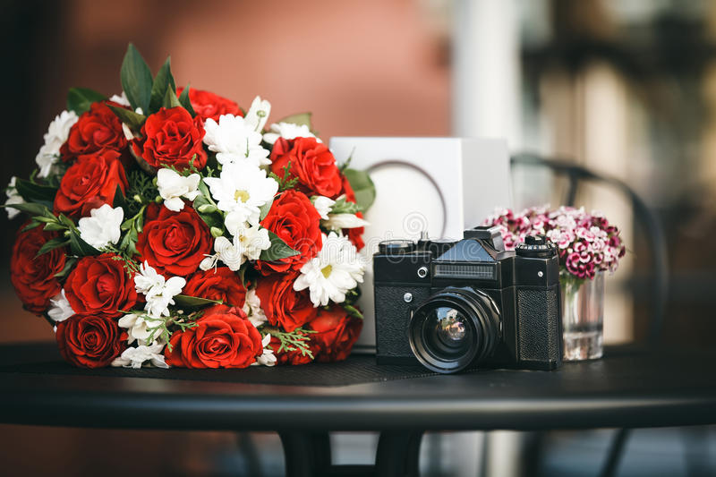 Composition of bouquet with red roses and chamomile and film cam stock photography