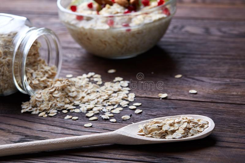 Composition with bowl of oatmeal porrige and dry oatmeal in glassware on vintage wooden table, selective focus royalty free stock photography