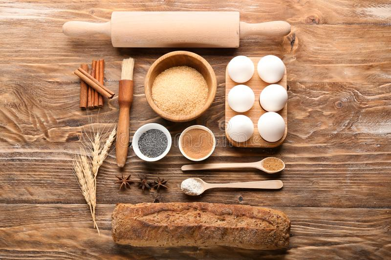 Composition with bread and ingredients for preparing bakery on wooden background stock images