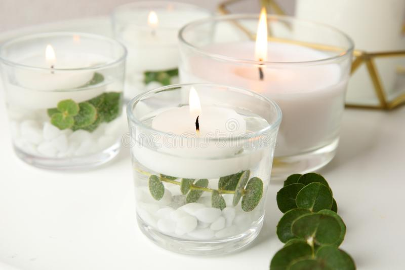 Composition with burning aromatic candles and eucalyptus. On table royalty free stock photo