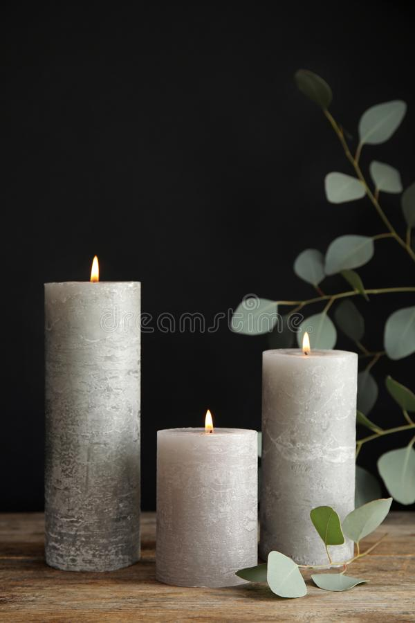 Composition with burning candles on table. Against black background royalty free stock photography
