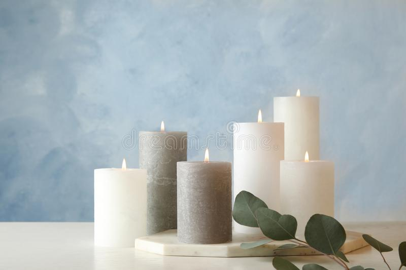 Composition with burning candles on table. Against color background stock photography