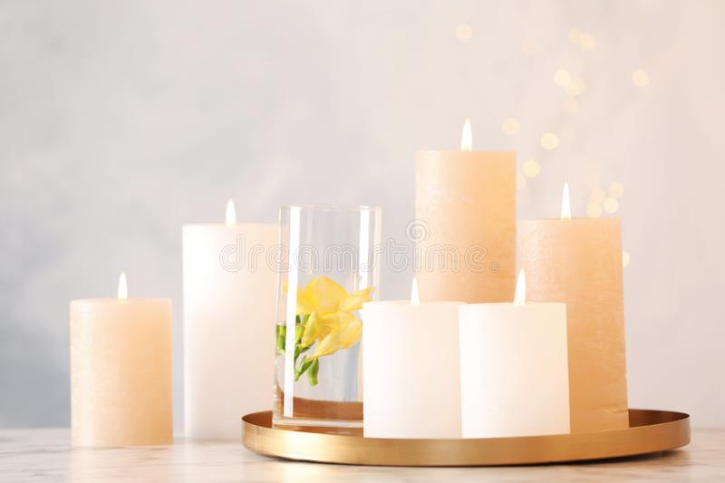 Composition with burning candles on table. Against light background stock image