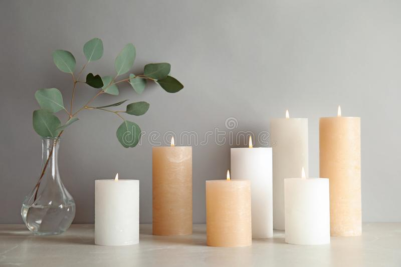 Composition with burning candles on table. Against light background royalty free stock photo
