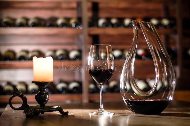 Composition of carafe, glass with wine and canddle. Shelves with wine bottles on a background. Composition of carafe, glass with wine and canddle. Shelves with stock image