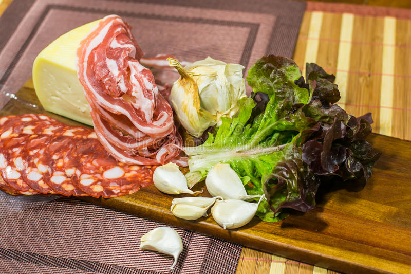 Composition of cheese, bacon, salami, violet - green lettuce and garlic on a wooden board royalty free stock photo