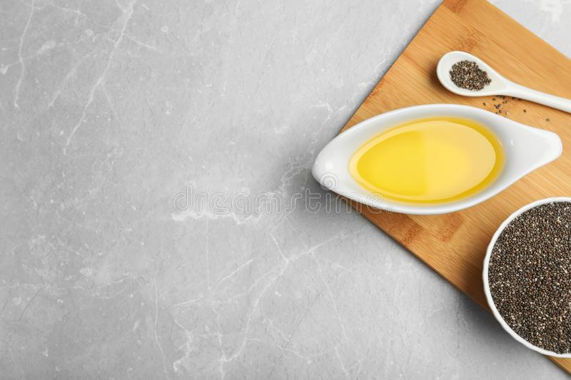Composition with chia seeds and sauce boat of oil on grey table, top view. Space for text stock images