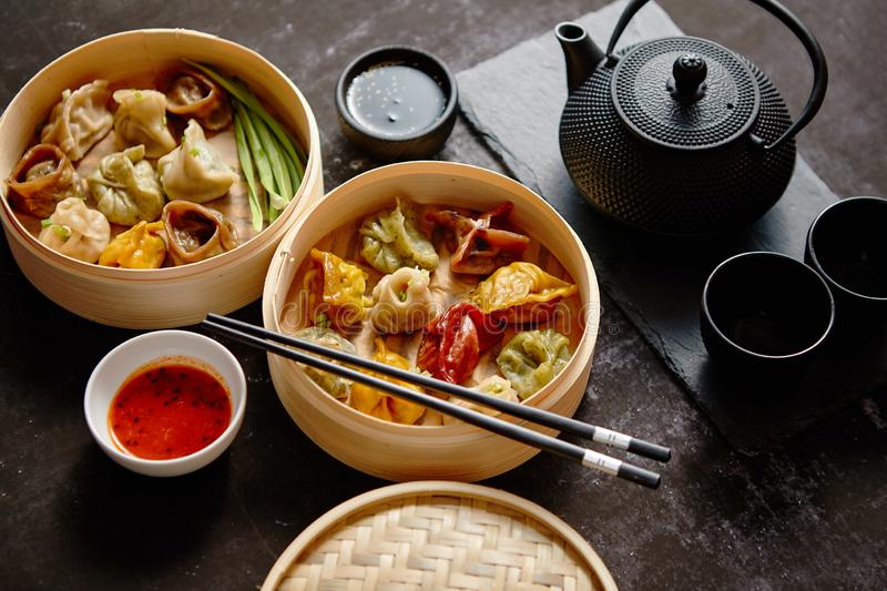 Composition of chinese food. Mixed kinds of dumplings from wooden bamboo steamer. Served with soy and spicy sauces and traditional tea in iron pot stock photo
