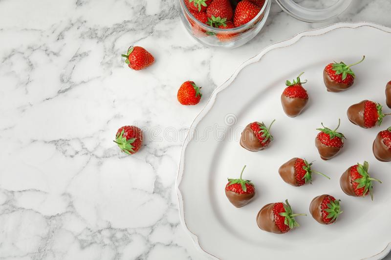 Composition with chocolate covered strawberries on marble background stock photo