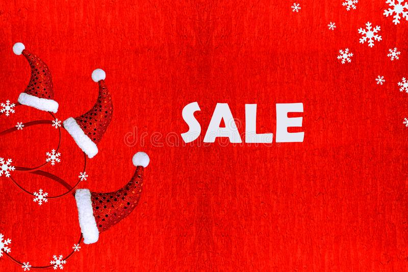Composition of Christmas red caps and snowflakes on a red background with the inscription sale. Concept for christmas, gifts, part stock images