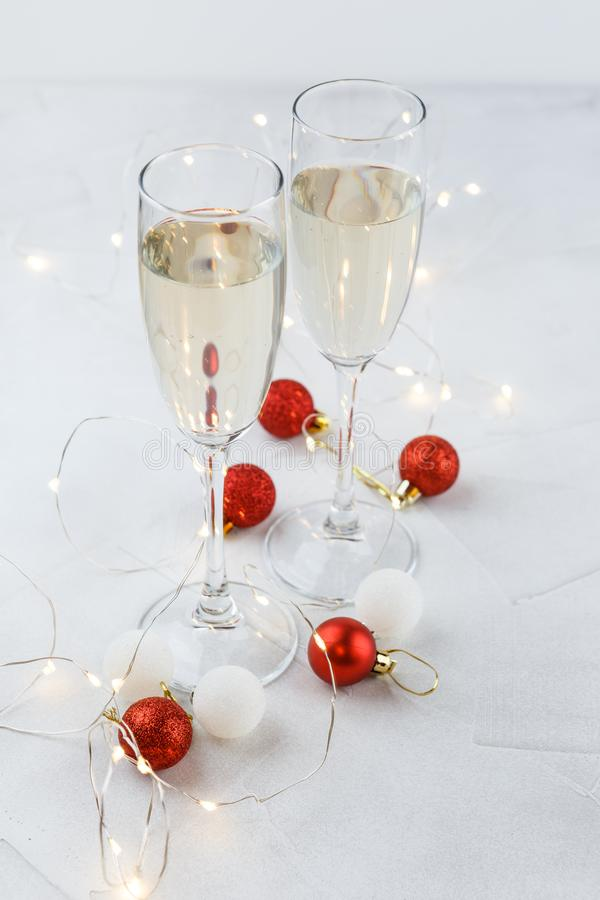 Christmas red balls and two glasses of champagne. Composition for Christmas with red and white balls, white lights and two glasses of champagne stock photo
