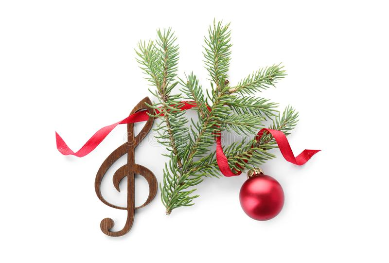 Composition with Christmas tree branch, decor and wooden music note on white background royalty free stock image