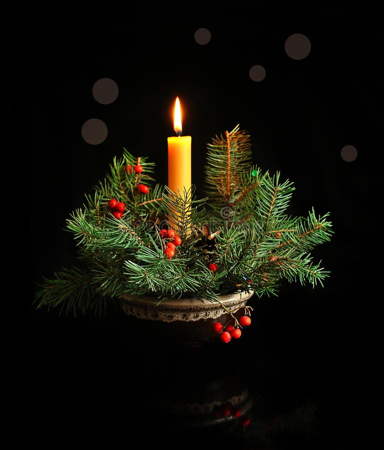 Composition from a Christmas tree branches and a burning candle on a dark background. Christmas and New Year stock photo