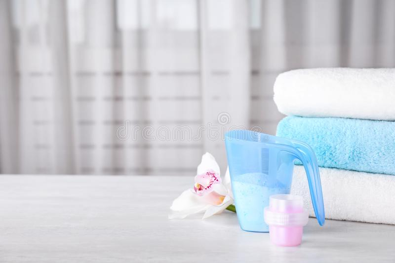 Composition with clean towels and laundry detergents on table against blurred background. Space for text stock photography